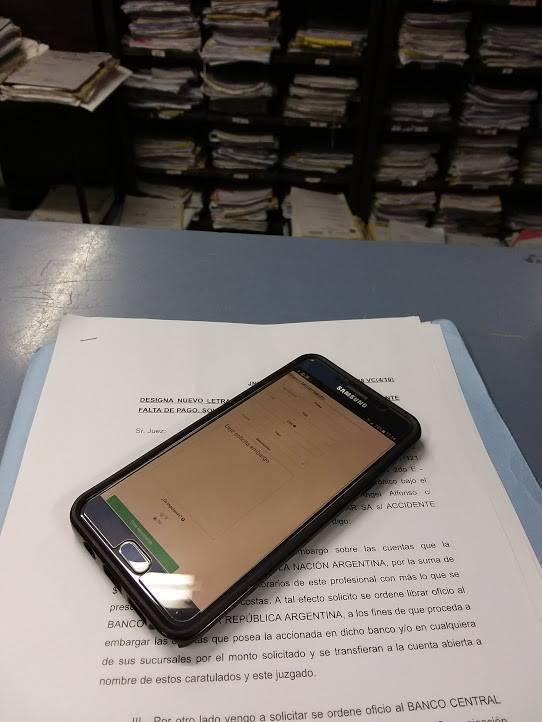 software para abogados - celular sobre mesa de entradas simbolizando carga de movimientos con el software para abogados